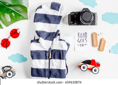 accessories for treveling with children, camera and suit on white background top view