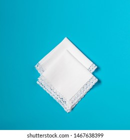 Accessories. Two white handkerchiefs with lace trim on a blue background with copy space.