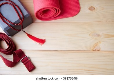 Accessories for yoga,pilates or fitness. Pink yoga mat, foam block,mala beads and red belt on wooden background with copyspace.