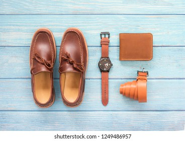 Men's accessory with loafer shoe, wallet leather, brown watch and belt  isolated on a blue wooden background. Top view.