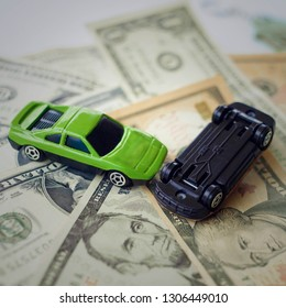 Accident between two toy cars on the background of dollar bills