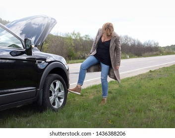 Accident and breakdowns with auto concept. Blonde woman and broken down car on road checking problem in engine