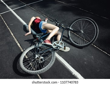 Accident.  A girl fallen off a bicycle and lying on the ground.