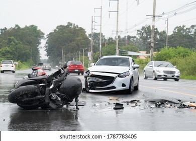 Accident with the motocycle or big bike and car in  bad weather driving with falling rain