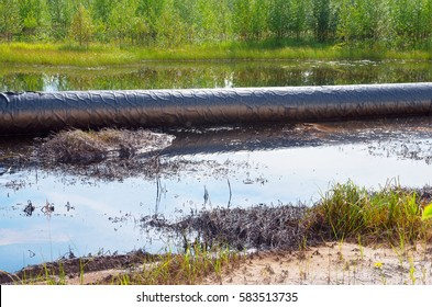 An accident on an oil pipeline. An oil spill around the pipeline.Environmental pollution.