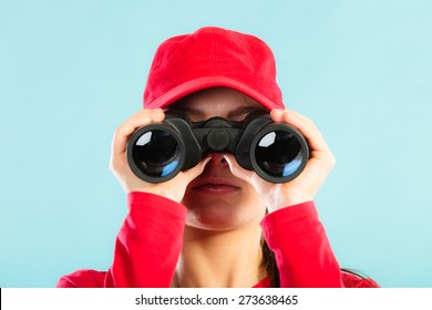 Accident prevention and water rescue. Closeup girl in red lifeguard outfit on duty looking through binocular on blue