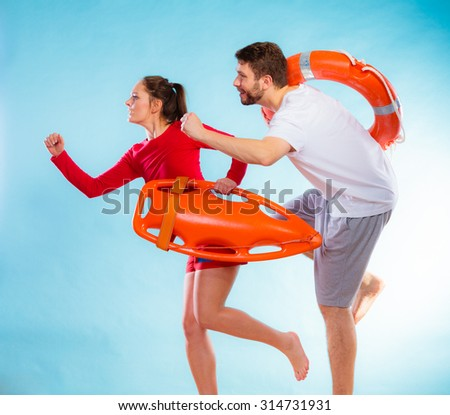 adbc968789f1 Accident prevention and water rescue. man and woman lifeguard couple on duty  running with with