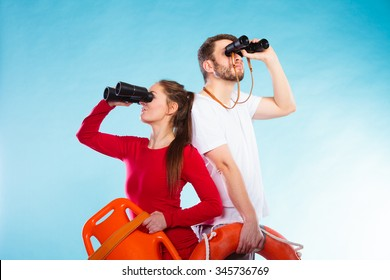 Accident prevention and water rescue. Young man and woman lifeguards on duty looking through binoculars keeping buoy lifesaver equipment on blue