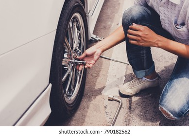Accident with punctured tires. Traveler Man changing flat tire on the road. Replacing the tires on the car,  Attaching a spare wheel.