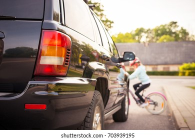 Accident. Small girl on the bicycle crosses the road in front of a car