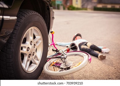 Accident. Small girl on the bicycle is hit by the car