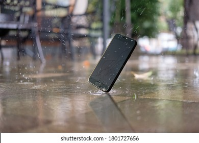 Accident with smartphone. Smartphone falling and crashing on wet ground in the city park on a rainy day, selective focus
