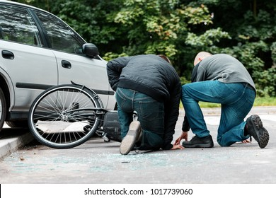 Accident witness helping an injured cyclist hit by a car