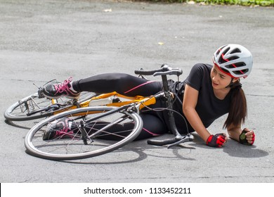 Accident woman on the street ground with a leg injury after falling off to her bicycle