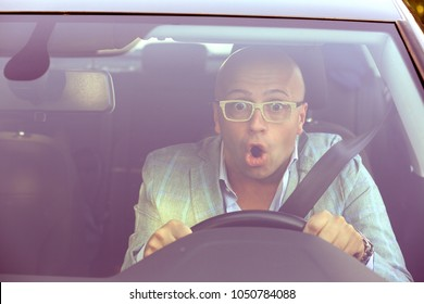 Accident. Young man driving a car shocked about to have traffic accident, windshield view