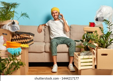 Accomodation and real estate concept. Cheerful man in fashionable clothes sits on couch, shares impression about new home to friend, has conversation via cell phone, poses around unopened boxes