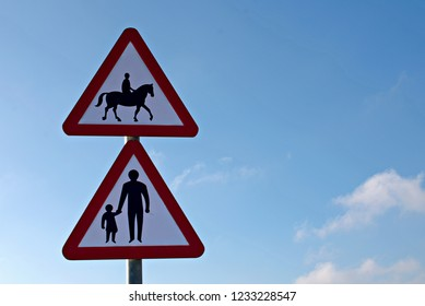 Accompanied Horses with Parent and child road signs, blue cloudy sky.