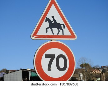 Accompanied Horses warning road sign. Person riding a horse inside red triangle above round 70 km/h speed limit sign. Outdoor rural and blue sky background. Haute-Garonne, southern France