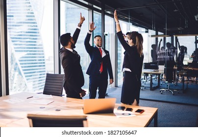 Accomplished male and female entrepreneurs collaborating togetherness on business idea brainstorming in modern office interior,happy crew in formal clothing giving five satisfied with approved project
