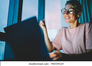 Accomplished student in eyewear feeling happy to compete course work late at night on laptop computer. Female freelancer receive job offer opportunity via email on netbook sitting at home in darkness