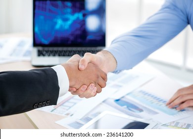 Accomplishment handshake deal. Confident businessman shaking hands with each other. Close-up view of the hands of a businessman in the office of the table in the formal wear.
