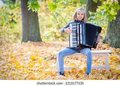 Accordionist in a park,  girl holding an accordion, professional accordionist.