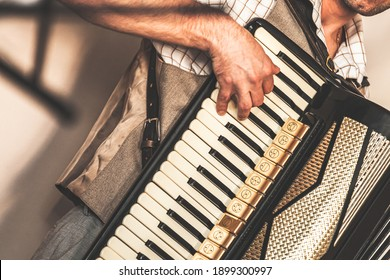 Accordionist plays accordion. Close-up photo with soft selective focus