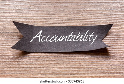 Accountability word written on Black papper with wooden background