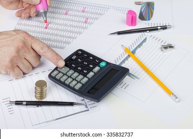Accountant balancing a sales ledger with a calculator