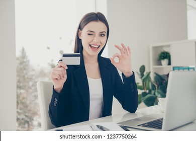 Accountant banker economist employer lady in formal wear with her brunette hair she sit on armchair chair look at camera hold credit card in hands wink eye show ok sign make beaming toothy smile