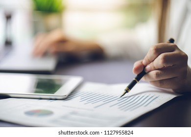 The accountant checking documents about graph and chart relating to financial reporting and tax accounting of the company. Picture is thin DOF selective focus at tip of fountain pen