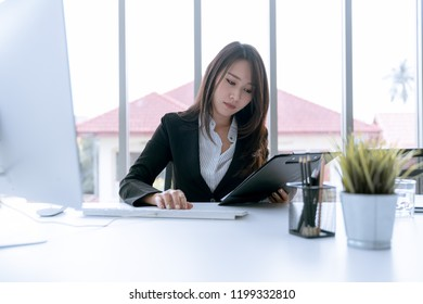 The accountant checking documents about graph and chart relating to financial reporting and tax accounting of the company