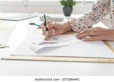 Accountant or financial adviser checking and comparing receipts while making a final report, working at her desk with calculator alongside.
