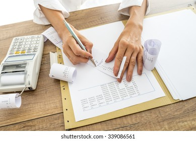 Accountant or financial adviser checking and comparing receipts and statistical data while making a final report, working at her desk with adding machine alongside.