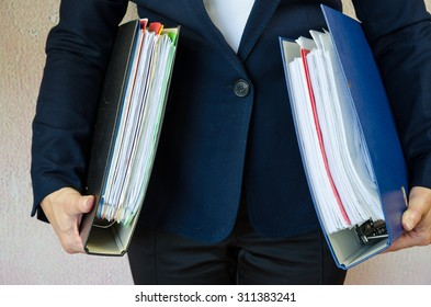 accountant with hands full of folders