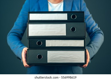 Accountant holding document binders with archived paperwork and other corporate legal sheets, mock up copy space
