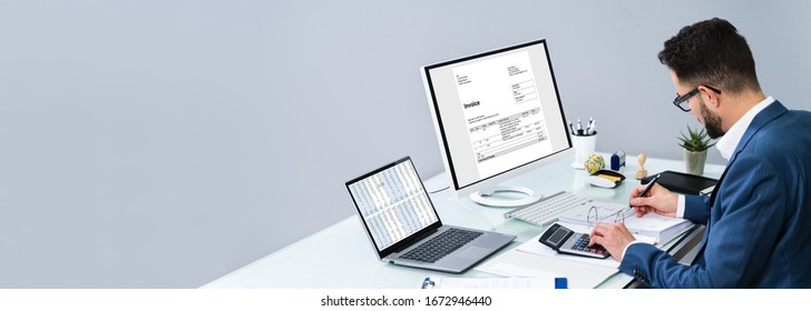 Accountant Making Invoice On Computer At Desk