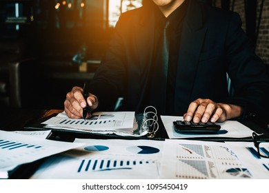 An Accountant man holding pen and using calculator do tax of company on wooden desk in office. freelance, tax, accounting, statistics and analytic research concept.