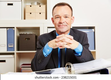 Accountant sitting at his desk in the office with files and a calculator