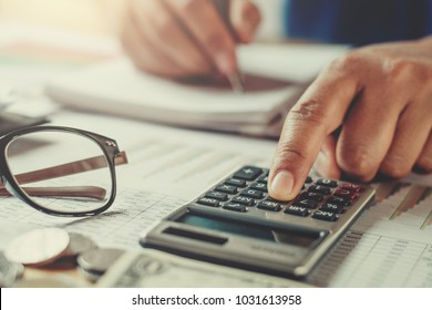 accountant using calculator to calculate budget on desk in office. concept finance and accounting