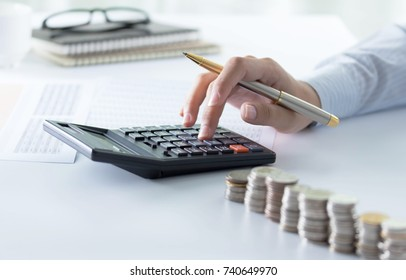 Accountant using calculator for checking numbers from balance sheet and financial statement. Concept of internal audit, accounting.