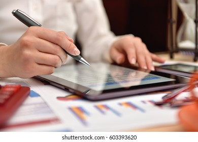 accountant woman analyzing income data and charts on digital tablet screen. Close up