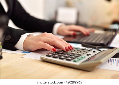 accountant woman considers on the calculator profit