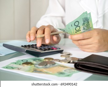 Accountant woman counting an australian money and using calculator for accounting concept.