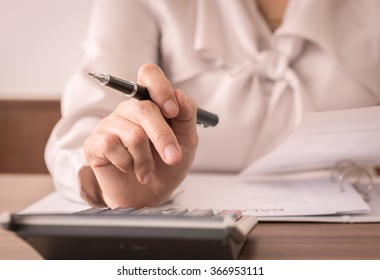 Accountant women or auditor using calculator for check the numbers on the balance sheet. Concept of accounting, bookkeeping,internal audit.