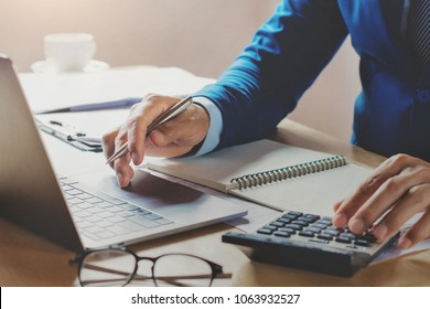 accountant working in office using laptop with calculator. concept business finance and accounting