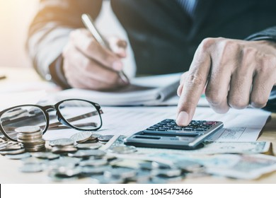 accountant working on desk in office using calculator to calculate budget. concept finance and accounting