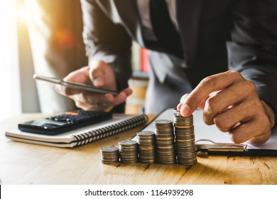 accountant working on desk in office using calculator and smartphone to calculate budget. concept finance and accounting in morning light