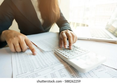 Accountant Working women uses calculator with Spreadsheet document, information financial concept