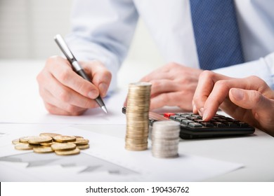 Accountants calculating profit - closeup shot of hands counting coins and making notes on paper